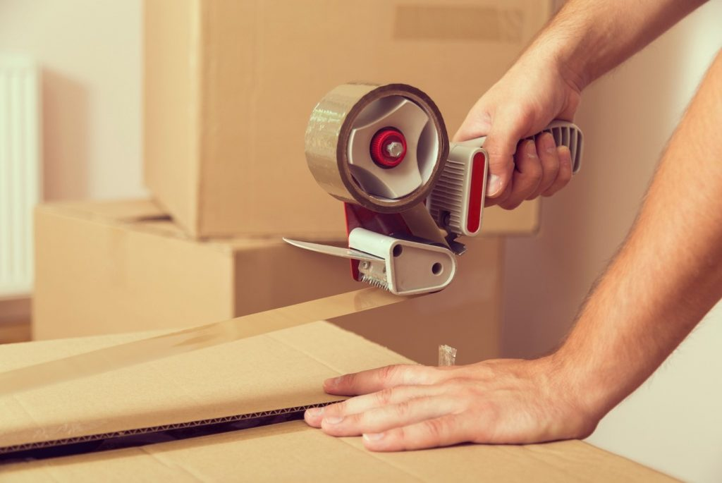 man packing box with brown packaging tape