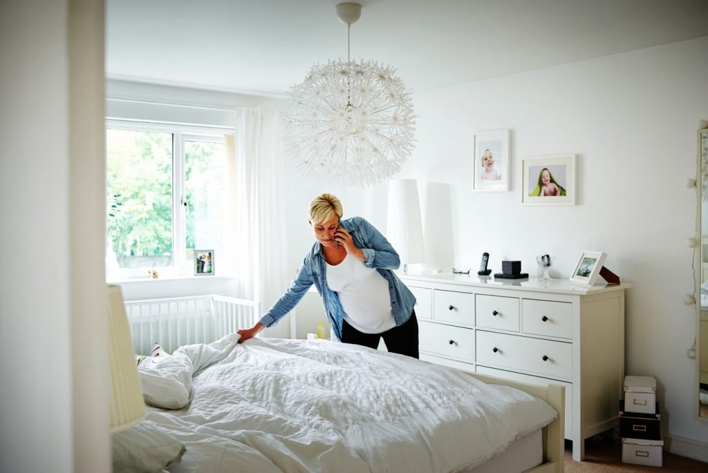 pregnant woman making the bed whilst on mobile phone