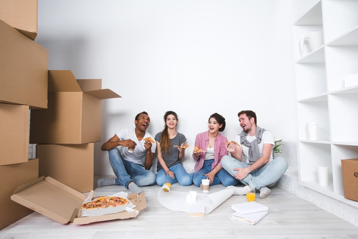 friends having pizza in empty room