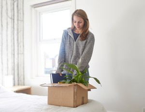 woman packing box wearing woolly jumper