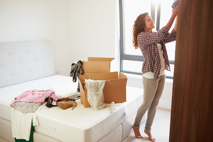 woman in bedroom packing clothes from wardrobe